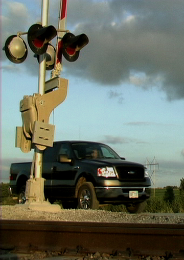 A railroad CEO conducts a sensitive business negotiation parked on a live railroad crossing in the Nebraska segment of We Pedal Uphill: Stories from the States, 2001-2008.